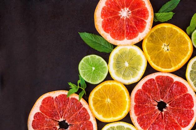 Hoek met schijfje sinaasappels, citroenen, limoenen, grapefruit en mint patroon op zwart. plat leggen
