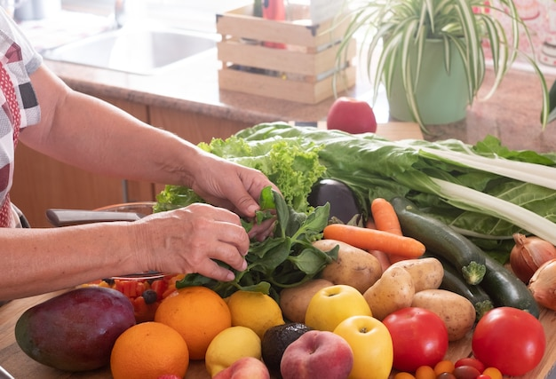 Hoek van de keuken en twee handen van een oudere vrouw die aan het werk is om een verse fruitsalade te maken. houten tafel met een grote groep kleurrijke groenten en fruit. gezond eten