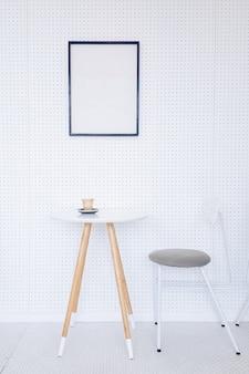 Hoek van een keuken met een tafel, grijze stoelen en een poster die op een lichtgrijze muur hangt.
