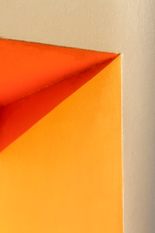 Hoek van een oranje muur en schaduw