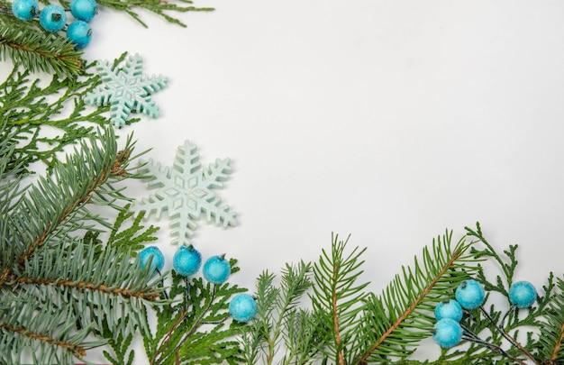 Hoek van het frame gemaakt van kerstboomtakken, sneeuwvlokken en blauwe bessen
