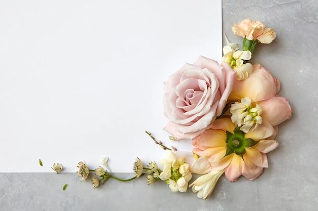 Hoekframe van bloemen en een wit papier op een grijze achtergrond, plat gelegd