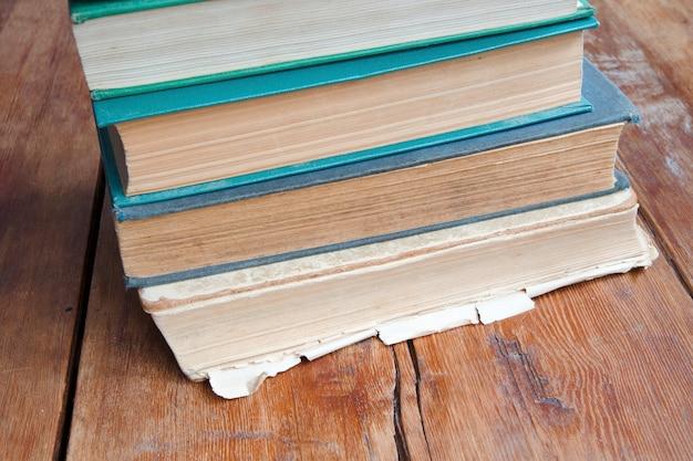 Hoekmening aan stapel oude boeken die op het uitstekende houten tafelblad leggen