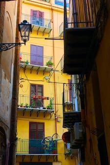Hoekmening van smalle zijstraat met kleurrijk geel huis uiteindelijk in palermo, sicilië, italië