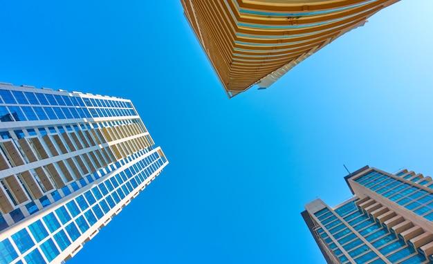 Hoekopname van moderne flatgebouwen met meerdere verdiepingen tegen de heldere blauwe lucht