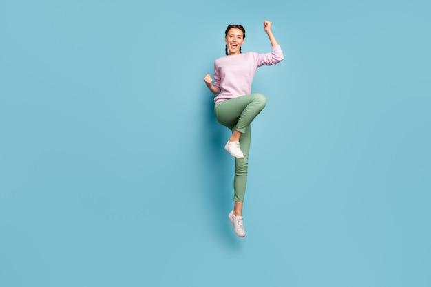 Hoera! full body foto van grappige dame springen hoog goed humeur win sportieve wedstrijd kampioenschap dragen casual roze trui groene broek schoenen geïsoleerde blauwe kleur