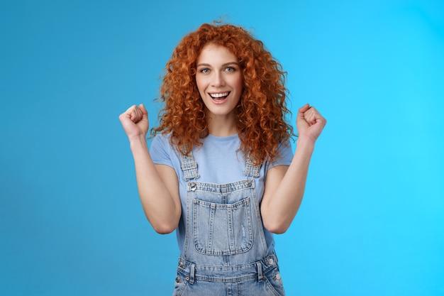Hoera geslaagde dag. vrolijke christelijke roodharige meisje zomer tuinbroek balde vuisten vreugdevol glimlachend breed vastbesloten succes te behalen, zegevierend winnend spel staande vrolijke blauwe achtergrond.