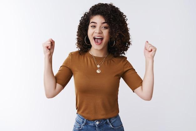 Hoera goed nieuws. aantrekkelijk succesvol gelukkig jong meisje donker krullend haar juichen ondersteunende vriend balde wijsvingers opgeheven overwinningsgebaar vieren feliciteren met vriend vreugdevol glimlachen
