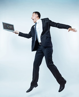 Hoera. zeer emotionele volwassen man in een zwart pak kan niet op één plek staan en hoog springen terwijl hij met een wijd geopende mond naar een scherm van zijn laptop kijkt.