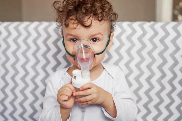 Hoestbehandeling door inademing. baby met een verstuiver in zijn handen, ademmasker op zijn gezicht