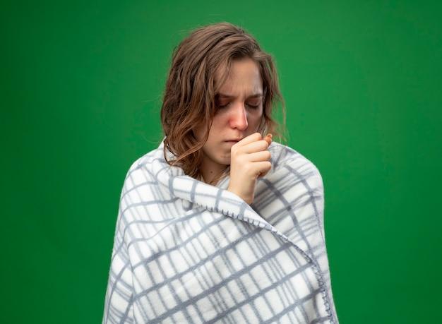 Hoesten jong ziek meisje met wit gewaad verpakt in geruite hand op mond geïsoleerd op groen