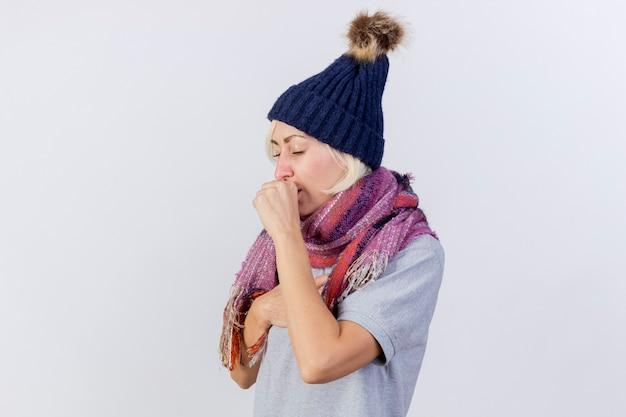 Hoesten jonge blonde zieke vrouw met winter hoed en sjaal houdt vuist dicht bij mond geïsoleerd op een witte muur