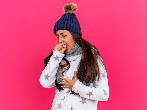 Hoesten ziek meisje dragen winter hoed met sjaal bedekt mond met hand geïsoleerd op roze
