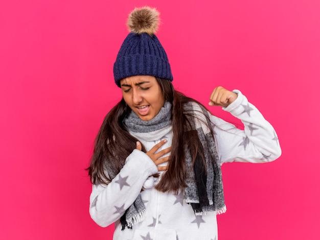 Hoesten ziek meisje met gesloten ogen dragen winter hoed met sjaal geïsoleerd op roze
