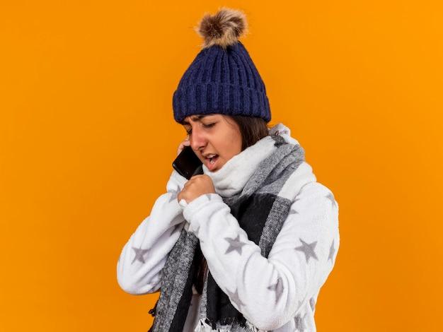 Hoesten ziek meisje met gesloten ogen dragen winter hoed met sjaal hand rond mond geïsoleerd op gele achtergrond te houden