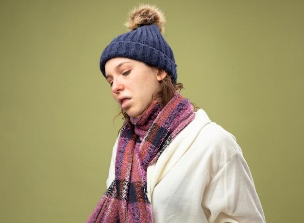 Hoesten ziek meisje met witte mantel en muts met sjaal geïsoleerd op olijfgroen