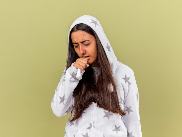 Hoesten ziek meisje zetten kap met hand op kin geïsoleerd op olijfgroene achtergrond