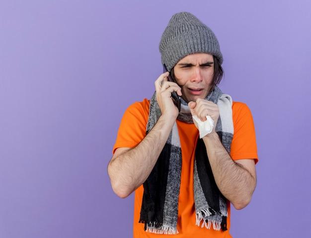 Hoesten zieke jongeman met winter hoed met sjaal spreekt op telefoon geïsoleerd op paarse achtergrond