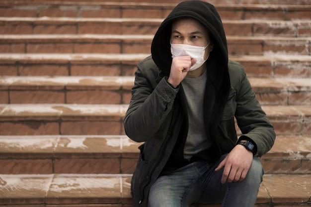 Hoestende man die zich voordeed op de trap terwijl het dragen van medisch masker
