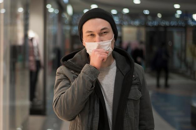 Hoestende man in het winkelcentrum met medisch masker