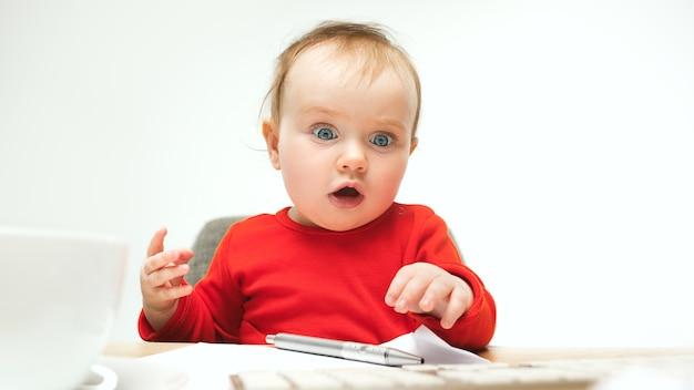 Hoeveel documenten kan ik kind babymeisje zitten met toetsenbord van moderne computer of laptop in witte studio ondertekenen.