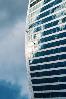 Hoge arbeiders wassen ramen op de muur van een gebouw