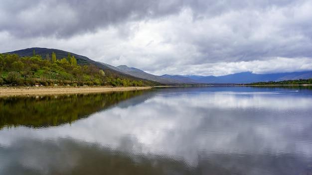 Hoge bergmoeras met reflecties in het water en dramatische hemel met grote wolken. lozoya madrid.