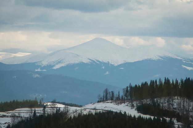 Hoge besneeuwde berg in mistig weer en wolken