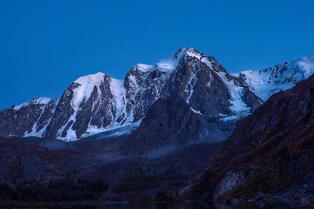 Hoge besneeuwde bergen verlicht door het licht van de maan in een heldere hemel in de schemering.