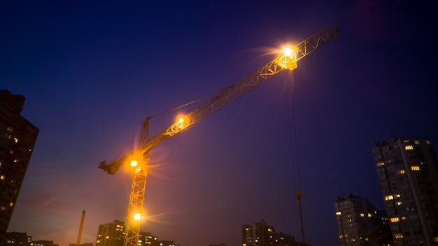 Hoge bouwkraan die 's nachts werkt