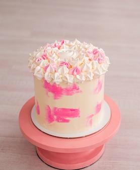 Hoge cake met roze uitstrijkjes. fijne cake met schuimgebak voor meisjes