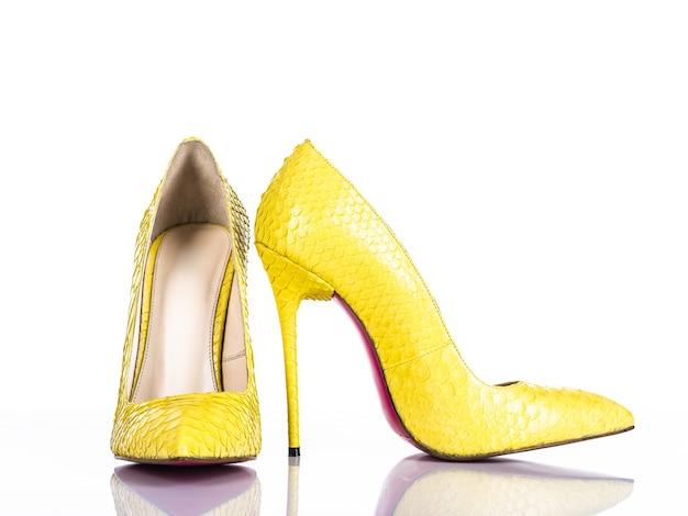 Hoge de hielschoen van de modieuze vrouw die op witte achtergrond wordt geïsoleerd. mooie gele vrouwelijke hoge hakenschoen. luxe.