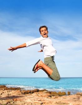 Hoge de vliegsprong van de jongenstiener op strand blauwe hemel