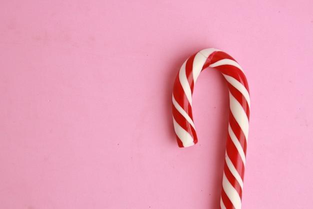 Hoge die hoek van een heerlijke suikergoedstok is ontsproten die op een roze oppervlakte wordt geïsoleerd