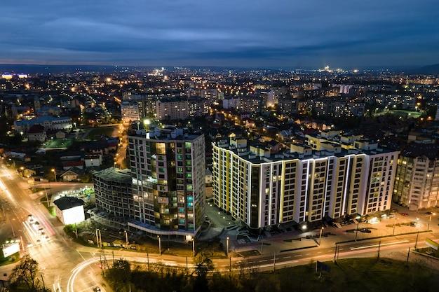 Hoge flatgebouwen met verlichte ramen in de woonwijk van de stad 's nachts.