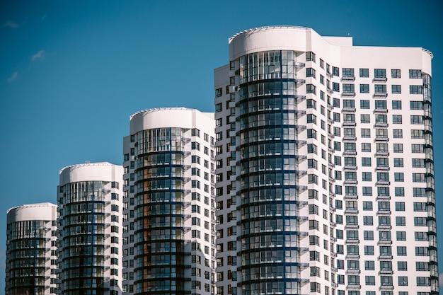 Hoge flatgebouwen op een achtergrond van blauwe hemel