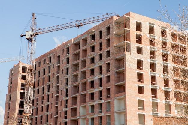 Hoge gebouwen met meerdere verdiepingen in aanbouw. torenkranen dichtbij gebouw. activiteit, architectuur, ontwikkelingsproces, wolkenkrabber.