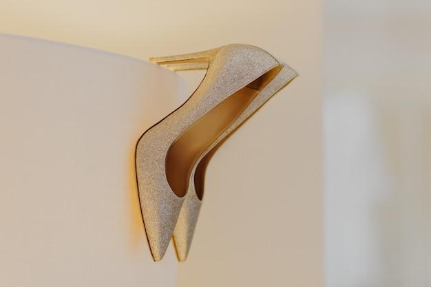 Hoge hakken zilveren schoenen voor bruid tegen witte achtergrond