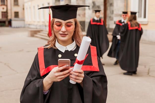 Hoge hoek afgestudeerd meisje met mobiel