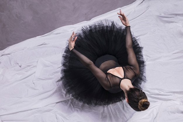 Hoge hoek ballerina zit binnenshuis