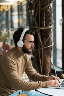 Hoge hoek bedrijfsmens met hoofdtelefoons het werken