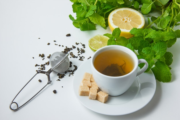 Hoge hoek bekijken een kopje thee met citroen, suiker, muntblaadjes op witte ondergrond. horizontaal