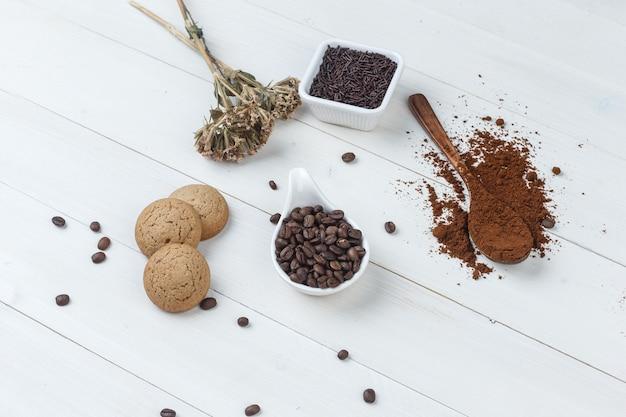 Hoge hoek bekijken koffie in beker met gemalen koffie, koffiebonen, gedroogde kruiden, koekjes op houten achtergrond. horizontaal