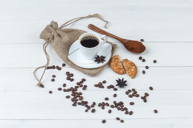 Hoge hoek bekijken koffie in beker met gemalen koffie, kruiden, koffiebonen, koekjes op houten en zak achtergrond. horizontaal
