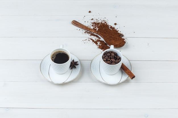 Hoge hoek bekijken koffie in beker met gemalen koffie, kruiden, koffiebonen op houten achtergrond. horizontaal