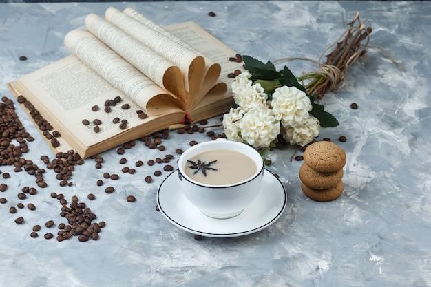 Hoge hoek bekijken koffie in beker met koekjes, koffiebonen, bloemen, boek op grijze gips achtergrond. horizontaal