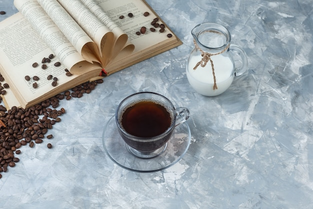 Hoge hoek bekijken koffie in beker met koffiebonen, boek, melk op grungy grijze achtergrond. horizontaal