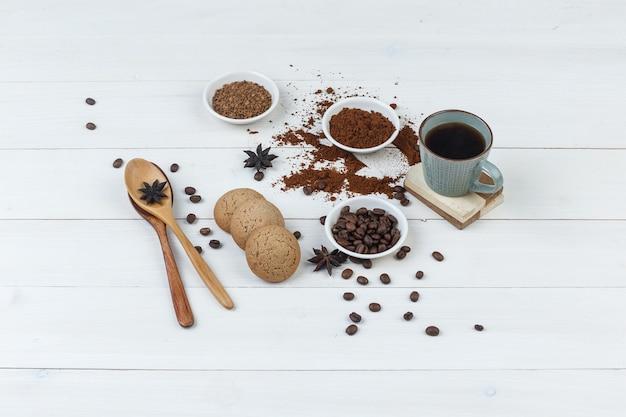 Hoge hoek bekijken koffie in beker met koffiebonen, gemalen koffie, kruiden, koekjes, houten lepels op houten achtergrond. horizontaal