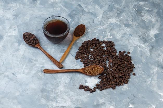 Hoge hoek bekijken koffiebonen, kopje koffie met oploskoffie, koffiemeel, koffiebonen in houten lepels op lichtblauwe marmeren achtergrond. horizontaal