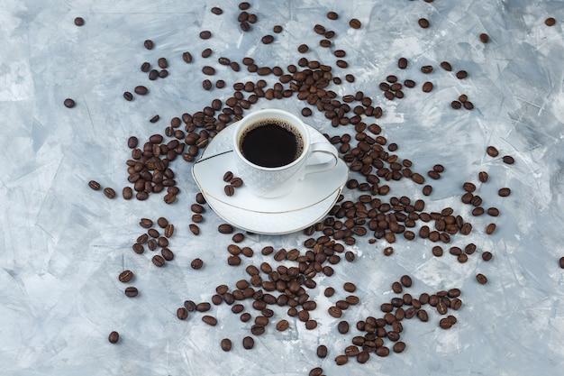 Hoge hoek bekijken koffiebonen, kopje koffie op lichtblauwe marmeren achtergrond. horizontaal
